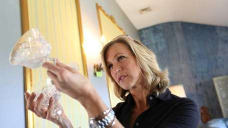 Lara Spencer inspects wine glasses at a tag