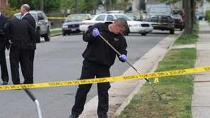 Nassau detectives and police officers investigate the scene