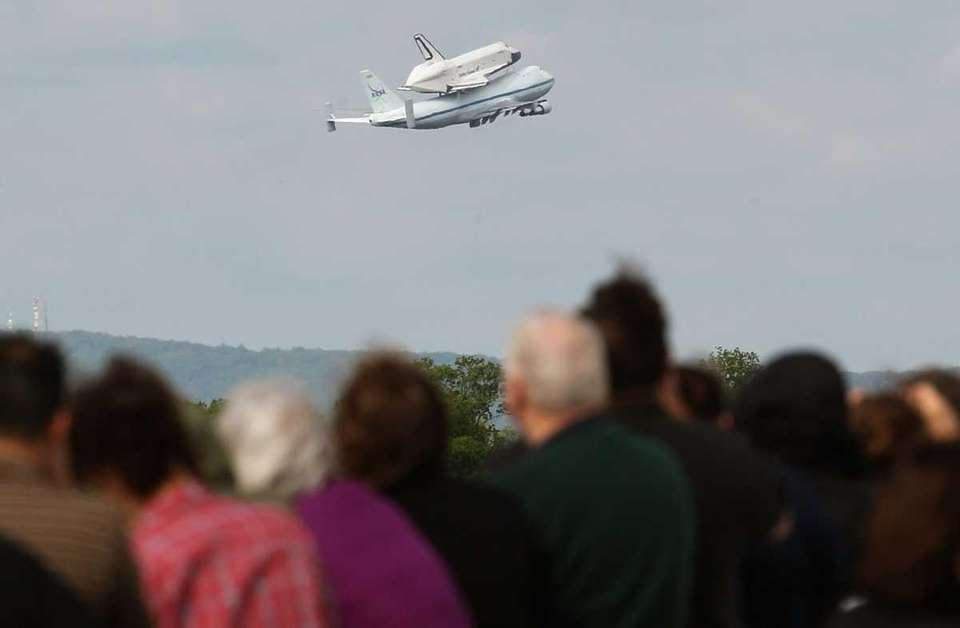 People watch as the Space Shuttle Enterprise takes