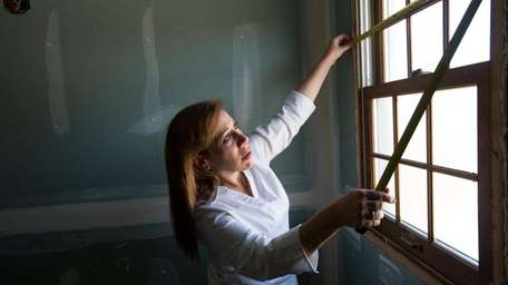 Sheryl Keane measures a window for blinds in