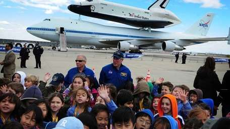 Children gather in front of the Space Shuttle