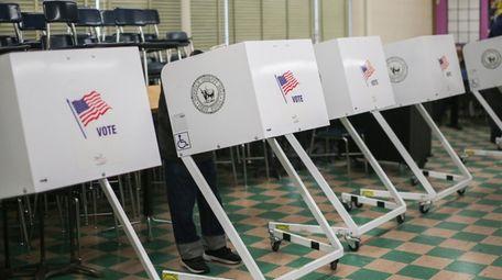 A voter casts a ballot at West Babylon