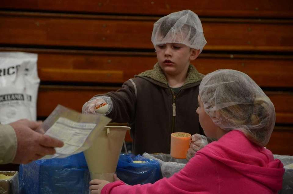 Quinn Broggy, 7, of Syosett, helps pack meals