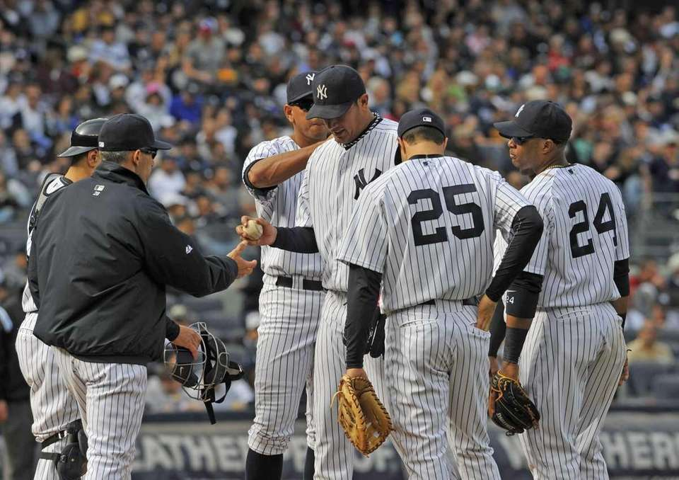 Freddy Garcia hands the ball to Yankees manager