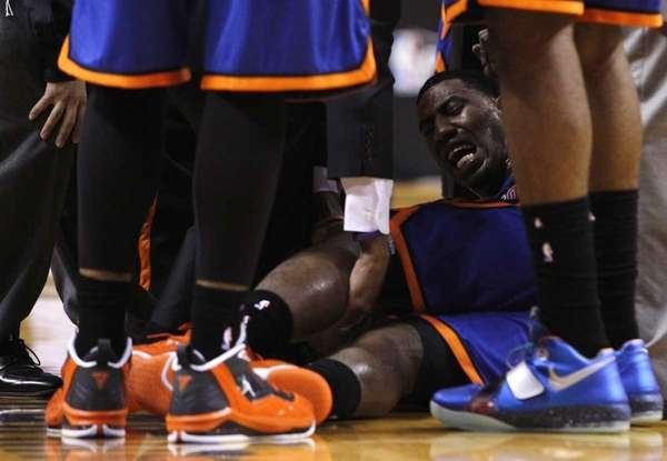 Iman Shumpert, center, is helped up from the