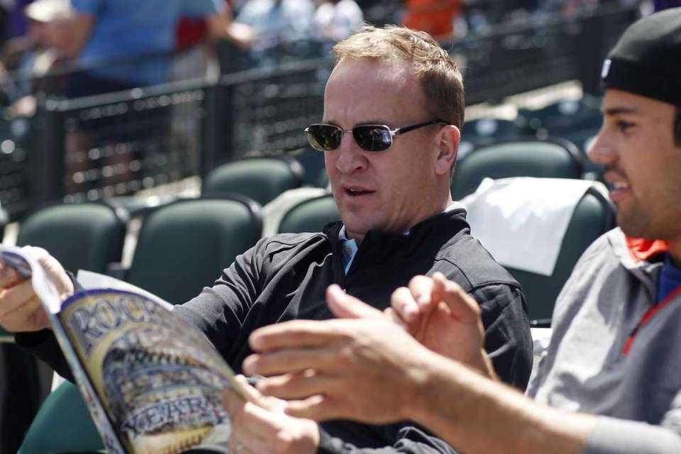 Denver Broncos quarterback Payton Manning, left, looks over