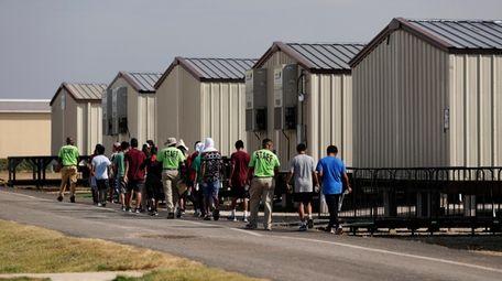 Staff escort immigrants to class at the U.S.
