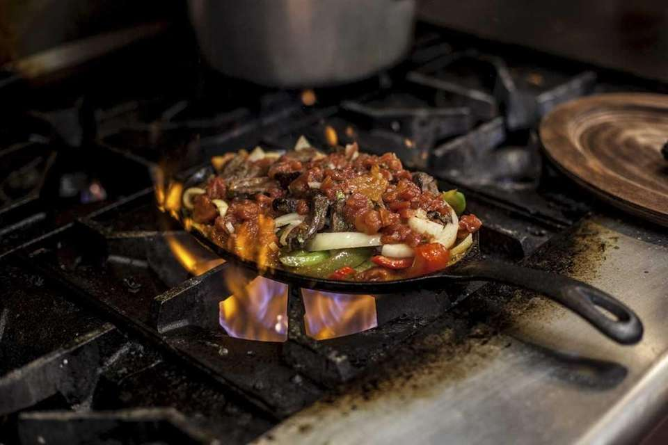 A beef fajita platter cooks on the stove