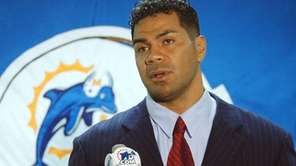 Junior Seau talks to the media during a