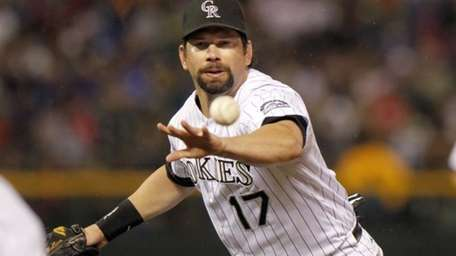 Colorado Rockies first baseman Todd Helton throws out