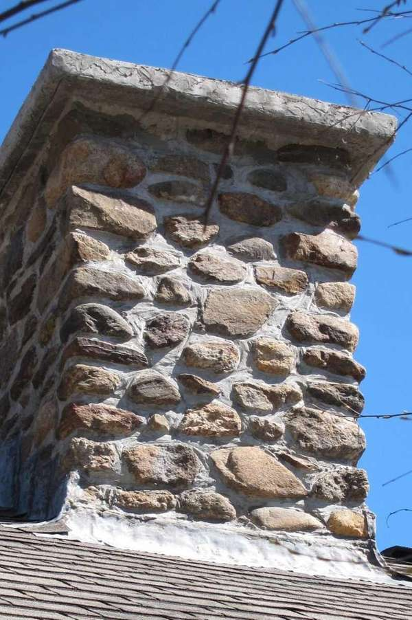 This stone chimney has a properly constructed top