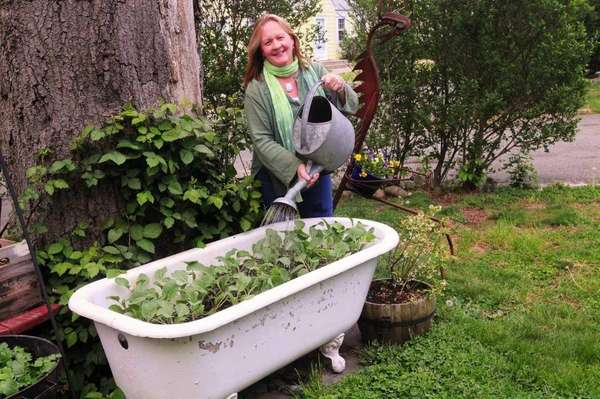 Betsy Davidson waters a claw-footed bathtub, which she