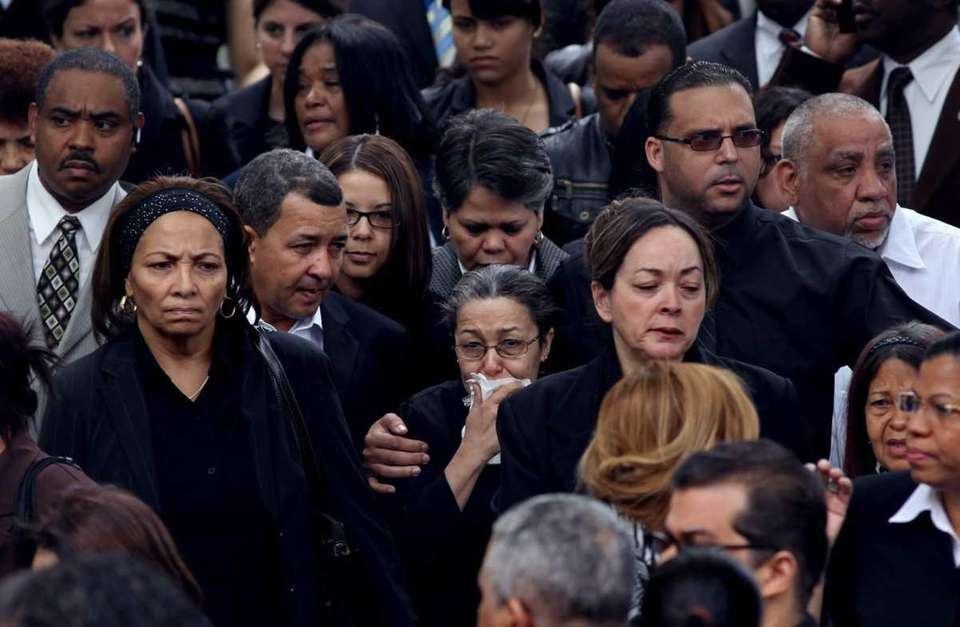 Mourners pour from the Church of Saint Raymond
