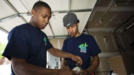 Green Earth Insulation employees Kaisean Mays, left, and