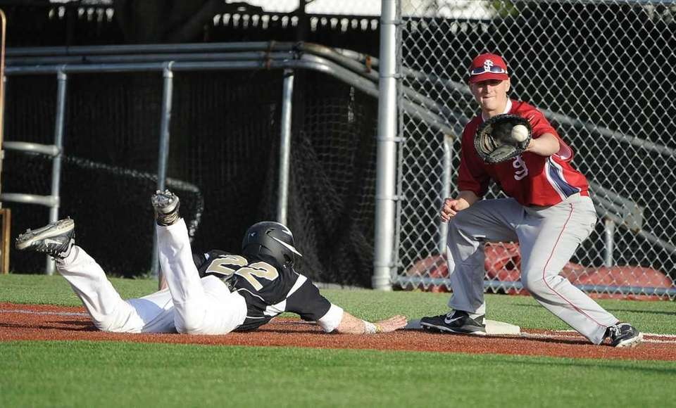 St. Anthony's Mike D'Acunti dives safely back to