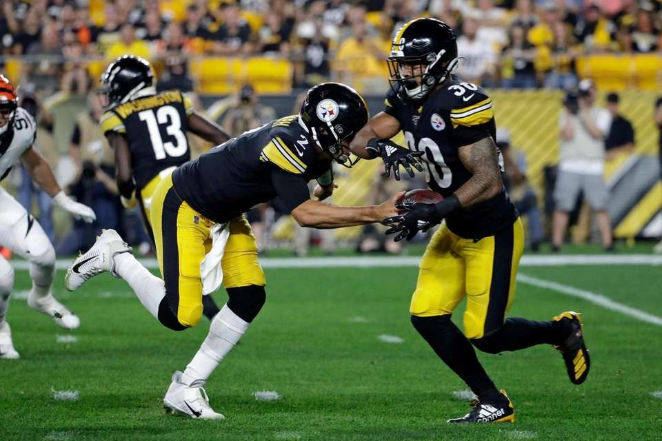 Pittsburgh Steelers quarterback Mason Rudolph hands off to