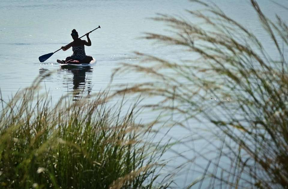 A paddle boarder makes their way through the