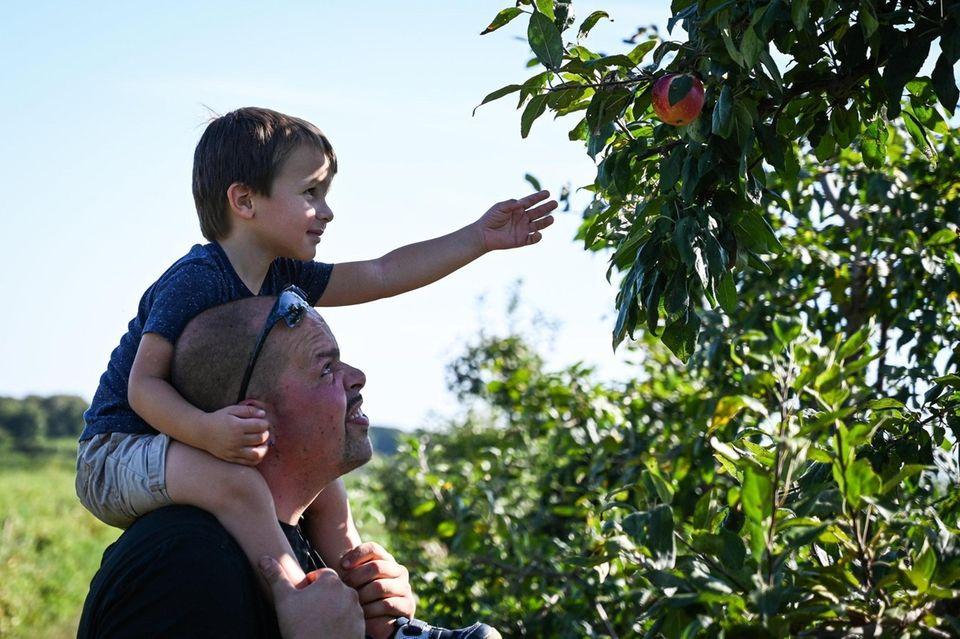 Antonio Martinez, of Mastic Beach, lifts his son