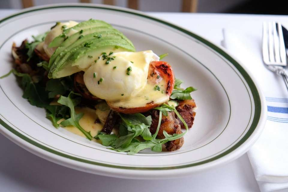 Eggs Benedict with arugula, roasted tomatoes and avocado,