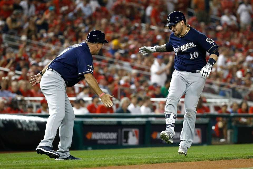 Milwaukee Brewers' Yasmani Grandal, right, rounds the bases