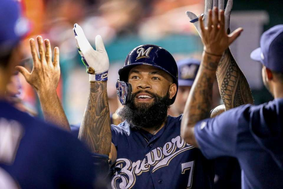 Milwaukee Brewers' Eric Thames high fives teammates after