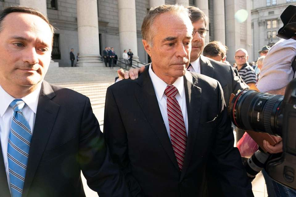 Former U.S. Rep. Chris Collins, center, arrives at