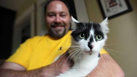 Kevin Vallas holds his cat Jinxy at his