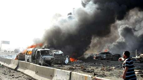 Burning vehicles at the site of twin blasts