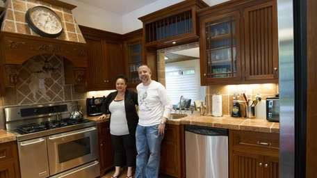 The Kauffmans stand in the kitchen. The home