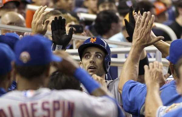 David Wright, center, celebrates in the dugout after