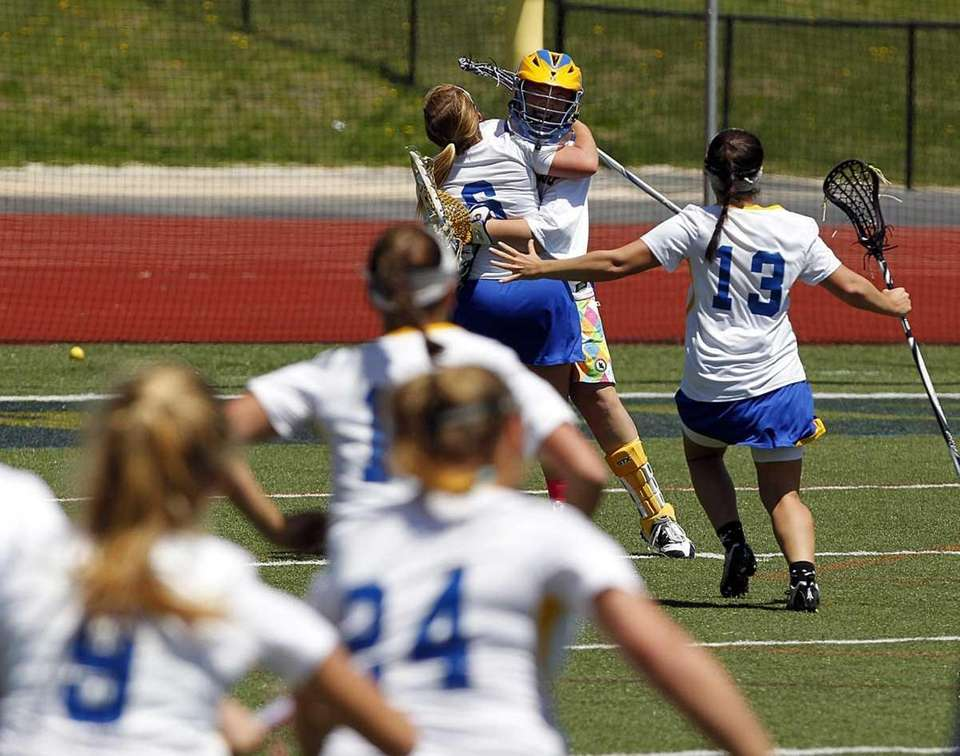 The Comsewogue girls varsity lacrosse team mob their