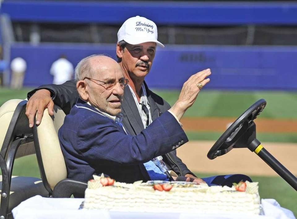 Yogi Berra gives a wave to the crowd