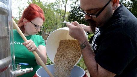Lauri and Matthew Spitz mash grain as they