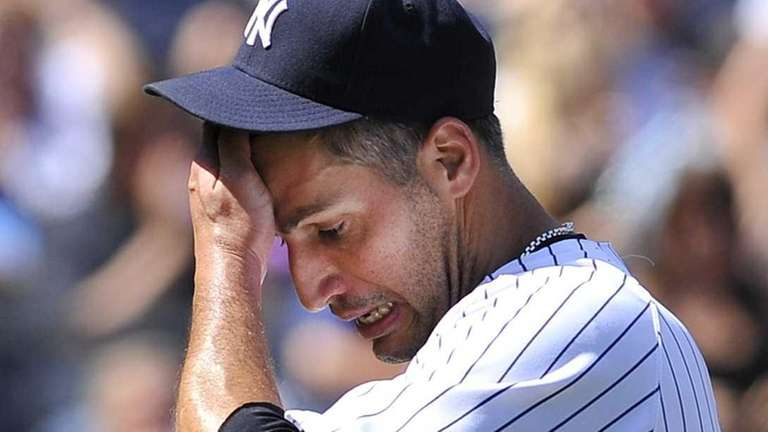 Andy Pettitte wipes his face as he heads