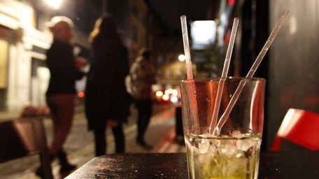 Two young women smoke outside a bar in