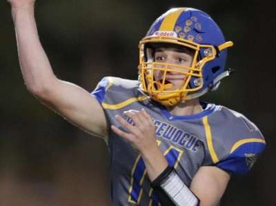 Comsewogue's Brady Shannon #11 throws a pass for