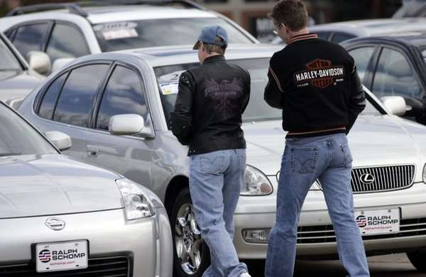 Shoppers look over unsold used vehicles at a