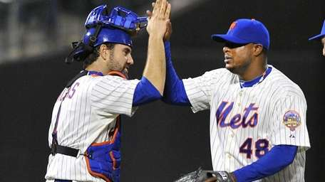 Mike Nikeas, left, and Frank Francisco high five