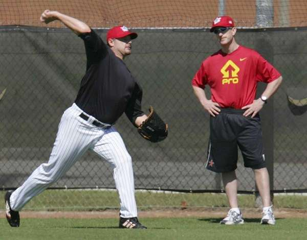 Roger Clemens, left, throws as strength coach Brian