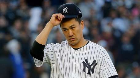 Masahiro Tanaka #19 of the Yankees walks to