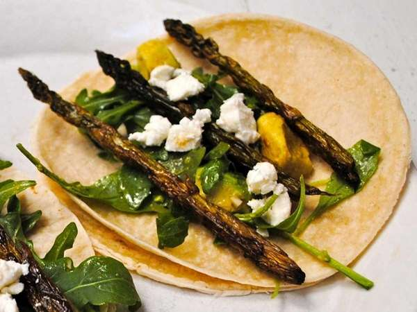 Combine roasted asparagus, arugula, avocado and goat cheese