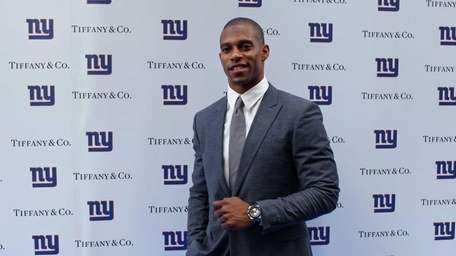 WR Victor Cruz stands for a photo as