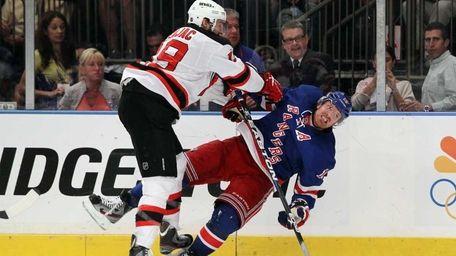 Travis Zajac of the New Jersey Devils checks
