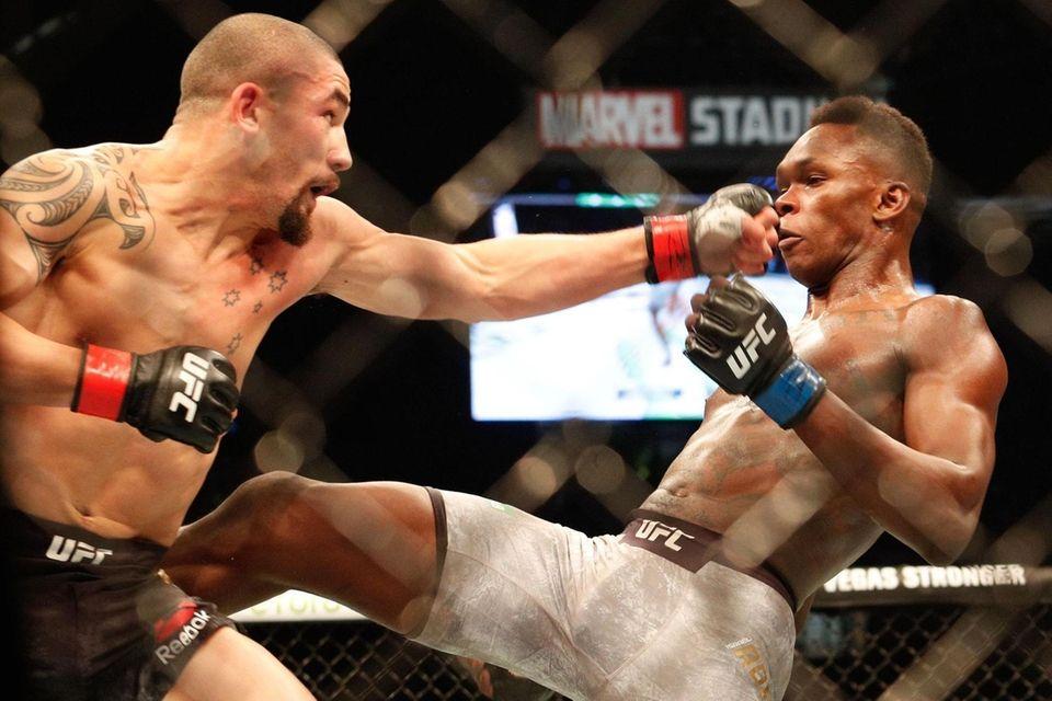 Robert Whittaker of Australia (L) punches Israel Adesanya
