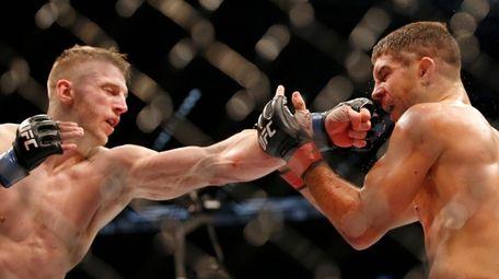 Dan Hooker of New Zealand punches Al Iaquinta