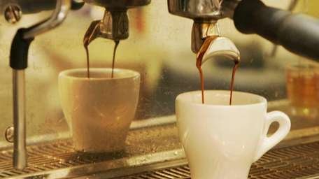 Espresso flows into a cup at a coffee