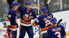 Islanders players celebrate Islanders center Brock Nelson's goal