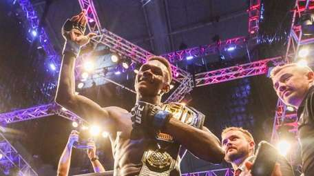 Israel Adesanya celebrates after defeating Robert Whittaker for