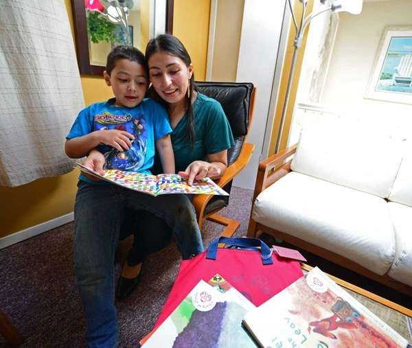 Rosa Maldonado and her son Nevin, 4, read