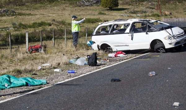 Policemen examine the scene of a minivan crash